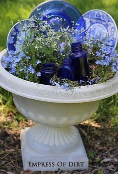 Early in the gardening season when the plants are small, I like to fill in the gaps with garden art. Here I've used some blue and white plates plus some old cobalt blue bottles to fill in this planter. When the flowers are larger (they'll spill over the edges), I'll remove the plates and bottles