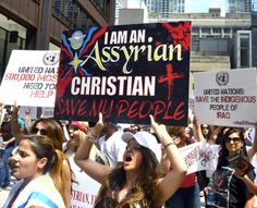 """Anna Enwia of Detroit chants """"Save our people. Free our land. Jesus is our savior. Stop ISIS now..."""" at a rally Friday afternoon at Daley Plaza where Assyrian Christians are protesting their treatment in Iraq and Syria. 