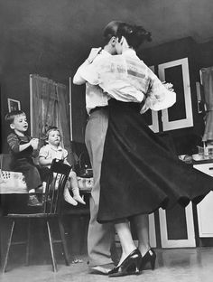 Children cheering as their parents dance in the kitchen. USA, 1950s