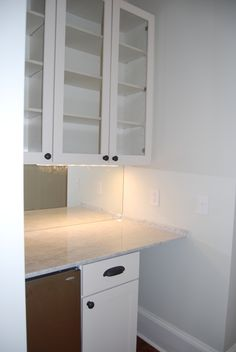 Solid wood cabinets, white carrara marble countertop, mirrored backsplash, glass-front wall cabinets, under-counter ice maker, and space for under-counter wine fridge