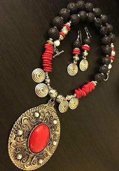 A LONG SET IN LAVA BEADS,CORAL AND TIBETAN SILVER PENDANT AND FINDING