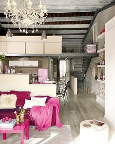 Not often I come by this combination, industrial loft with a color palette of pink! But I do love the pink SMEG fridge, it really ads some sweet flavor to this steal kitchen with Tolix chairs. The apartment has a cool mix of texture and materials. Soft furnishing, steel kitchen, romantic chandeliers next to industrial lamps. Creative and indeed very personal.