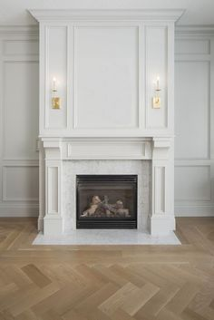 Traditional sitting room + herringbone flooring + white fireplace + wall paneling + art above fireplace + sconces on mantle + traditional fireplace design Fireplace Trim, Marble Fireplace Surround, Marble Fireplaces, Fireplace Wall, Living Room With Fireplace, Fireplace Design, White Mantle Fireplace, Fireplace Ideas, Simple Fireplace