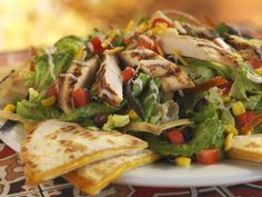 Quesadilla Explosion Salad: Grilled Chicken with cheese, tomatoes, corn relish, cilantro, tortilla strips and citrus-balsamic dressing. Served with cheese quesadillas. #Chilis