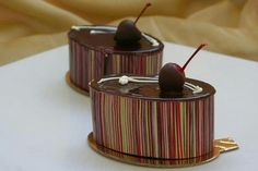 A layer of chocolate sponge cake under a center of chocolate mousse and sweet cherries, wrapped in a thin chocolate crust and topped with a chocolate dipped cherry.