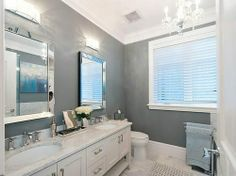 This Vancouver bathroom has marble tile flooring, gray walls, high ceilings, white trim, a marble counter, dual vanities, and a hanging chandelier.