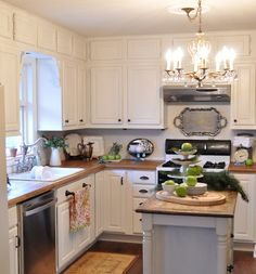 another beautiful kitchen re-do...paint those ugly oak cabinets a fresh, pretty white!  Butcher block countertops and wood floor are quite enough brown wood, IMO