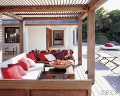 A wood-slat pergola shelters the outdoor seating area of a home on the island of Mustique.