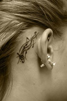 Music Staff notes tattoo behind the ear.  ouch!   A rather extreme way to let people know you have music in your ear :-)