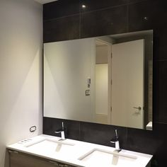Simple frameless wall mirror installed over a double sink.