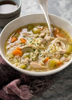 Easy chicken and rice soup in a rustic beige bowl, ready to be eaten.