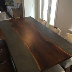 Concrete dining table with live edge slab by 910 Castings