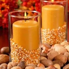 Butterscotch colored candle pillars in glass pillar vases filled half-way up with corn kernels set the mood for autumn.