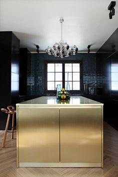 parisian loft by Studio ko black kitchen brass island