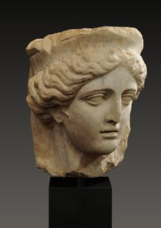 Roman marble head of Tyche, goddess of fortune and destiny, wearing a mural crown; from a relief. 1st - 2nd century CE.
