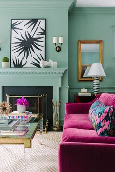 Green living room and fireplace with fuchsia pink sofas.