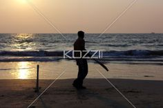 indians playing cricket - Playing cricket on Pollethai Beach, India during sunset.