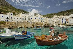 rowboats on clear blue waters in levanzo, italy.