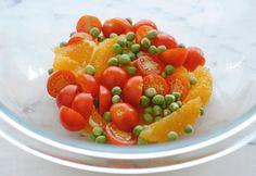 Combining the orange segments, tomatoes and peas