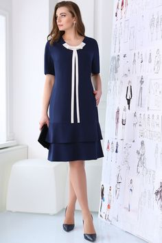 Элегантное платье полуприлегающего силуэта, с воланами по низу, с застежкой – «молнией»  в среднем шве спинке.  По переду нагрудные вытачки, в рельефных швах карманы. Спинка с талиевыми вытачками. Рукав цельнокроеный. Вырез горловины круглый, обработан обтачкой. Отделочным элементом является бант, с удлиненными поясками.