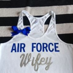 Air Force Wifey Tank White tank with Blue Lettering and Silver glitter lettering complete with a blue bow :) This is a 50/50 poly cotton blend tank, size chart attached to help with sizing questions!