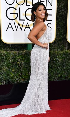 GINA RODRIGUEZ in a flirty silver fringe Naeem Khan halter dress and Chopard gems.