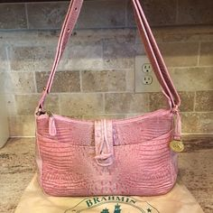 NWOT Brahmin Pink Crocodile Hobo Bag This is a great croc Brahmin NWOT bag & its duster. It's a gorgeous pastel pink color and has a surprising amount of pockets for a slim hobo. There is a large one on the front plus 4 open pockets and a 5th zipped one inside. It also has a key clip and 2 pen holders made from the pink croc inside. It is a seriously beautiful bag! Brahmin Bags Hobos