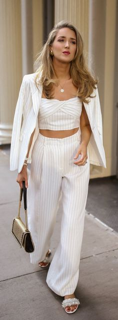 Monochrome dressing, back with a vengeance // White pinstripe suit with coordinating twist-front crop-top + high-waist pleated wide-leg pants, white slide sandal shoes with ruffle details, gold statement earrings, stacked gold bracelet, woven faux leather flap shoulder bag {Rachel Zoe, Stella McCartney, Roxanne Assoulin, classic style, monochrome dressing}