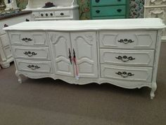 SOLD - This charming French country 9 drawer dresser is painted creamy white and lightly distressed. It measures 74 inches across the front and 20 inches deep.  It stands 32 inches tall.  It can be seen in booth H 13 at Main Street Antique Mall 7260 East Main St ( E of Power Rd ) Mesa 85207 480 924 1122 open 7 days 10 till 530 Cash or charge 30 day layaway also available