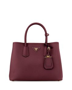 """Prada saffiano leather tote with golden hardware. Rolled top handles with strap keeper, 4.8"""" drop. Adjustable, removable shoulder strap, 23"""" drop. Open top with expandable snap sides. Leather triangle"""