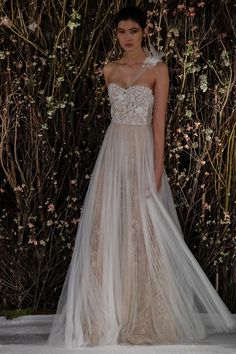 One shoulder beaded bodice Chantilly lace gown with plissé silk tulle skirt. Color: Nude Ivory