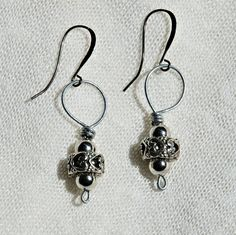 This is a pair of wire-wrapped earrings that features a couple cylindrical beads with a very pretty heart design on them!