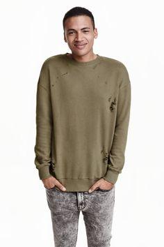 ダメージスウェットシャツ: ウォッシュ加工のスウェット素材を使用したトップス。ハードなダメージ加工が施されています。ドロップショルダーで、長袖。袖口と裾にリブ付き。