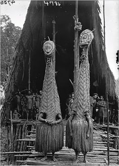 Papua New Guinea | Masked dancers in front of the men's longhouse at Tovei village. Urama Island, Gulf Province.  June 1921. | ©Frank Hurley, courtesy Australian Museum.