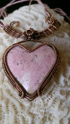 """This Beautiful One of a kind all Natural, untreated, Pink Rhodonite Heart, wrapped in Antiqued Copper is the perfect way to say I Love you!    The woven heart measures 1-3/4"""" x 1-1/4"""" and the necklaces adjusts from 18""""-20"""". Longer extender available.    KohlKraft Original!    A Taurus Birthstone, Rhodonite crystals are known for their capacity to bring emotional healing and to release blocked energy from within the heart chakra.    They have a strong heart based energy, that has a useful…"""