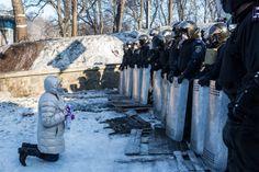 mujer de rodillas frente a policías anti disturbios