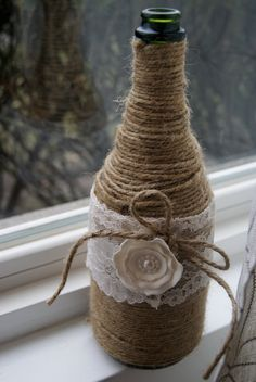 Twine wine bottle with lace and pearl flower-vase... @denise grant Hatch possible centerpieces for the dinner? I have easily 25 different size and shape drink bottles.