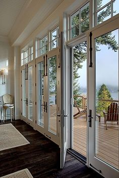 Gorgeous rustic chic white glass paned doors leading to the back deck.  From a 4-story Craftsman style home construction by Lavallee Construction, discovered on http://Porch.com