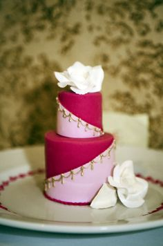 White roses top an individual wedding cake decorated in pink and gold. #WeddingCake