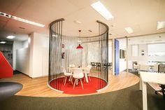 Oficinas de Meta4. Recepción con diseño de cuerdas. El diseño integra los colores corporativos (azul y rojo) y establece como hilo conductor un material de cuerdas tensadas, que permite configurar espacios de reunión informal o salas de brainstorming. Las cuerdas evocan ese significado de continuidad y unión.