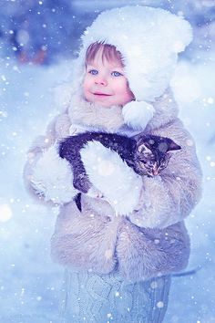 child holding a cat in the winter snow