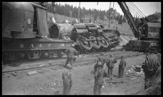 """Date: May 1930  Location: Homestake, MT Photographer: Mrs. Nels Brandal Railroad: Northern Pacific Railway Caption: """"Wreck of NP 2215, Class Q-4, light engine West, with Engr. Adams and work X1562, Class W, at Homestake, MT, May 1930. Two wreckers lifting the NP 2215. Wrecker BAP D-2 out of Butte and wrecker NP 41 out of Livingston. """""""