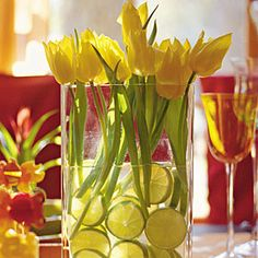 Bright yellow tulips and sliced limes together in a vase with simple lines make for a unique spring table centerpiece.