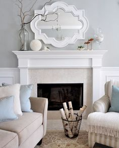 Chic living room design with gray walls paint color, Casbah mirror painted white, fireplace, tan sofa, blue pillows and wainscoting. by idlework