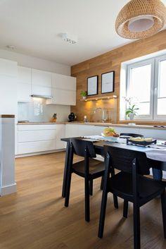 W aranżacji kuchni z jadalnią wykorzystano silny kontrast kolorystyczny. Zestawienie dwóch klasycznych barw - bieli oraz czerni - nadaje wnętrzu nieco elegancki charakter. Drewno ociepla aranżację, a pojedyncze dodatki wprowadzają ciepły, osobisty klimat.