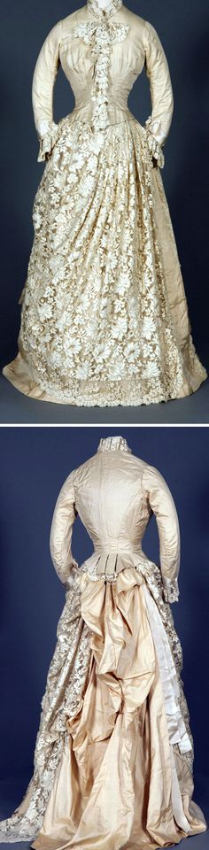 Four-piece ensemble of ivory silk satin & lace with taffeta trim, ca. 1870s. Basque bodice with ¾-length sleeves. Panel of lace at front of skirt, with fullness at back to accommodate bustle of satin and lace buttons with slight trim. Dark tan polished cotton underskirt; ivory satin cape with fringe. Worn as commencement dress. Vassar College Costume Collection