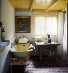 Rustic bath with brick floor, bright painted ceiling, antique table and weird urinal-looking sink.