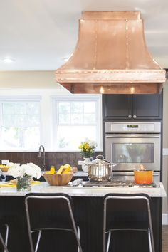 A copper range hood adds metallic glam to this traditional kitchen. Black kitchen cabinets with white granite countertops complement the classic, yet stunningly chic look. Black Kitchen Cabinets, Kitchen Hoods, Copper Kitchen, Kitchen Backsplash, Kitchen Countertops, Kitchen Black, Backsplash Ideas, Copper Backsplash, Smart Kitchen