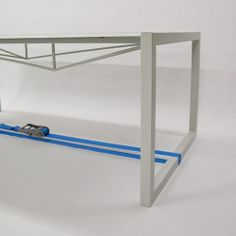 Stretched Table by Tom Cecil - A very thin sheet of steel is stretched across a steel frame to create a table. Supported only at the ends, the ratchet strap moves the base of legs together, the frame acting as lever, pulls the top tight with 30 ton of force.
