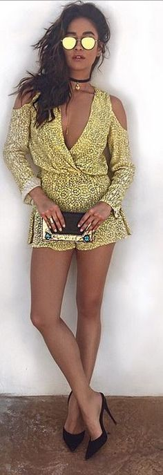 Who made Shay Mitchell's sunglasses, print clutch handbag, jewelry, and yellow print romper?